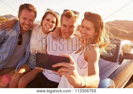 Friends On Road Trip Sit On Convertible Car Taking Selfie