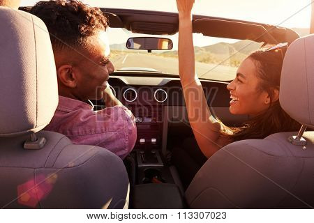 Couple On Road Trip Driving In Convertible Car