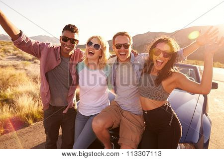 Friends On Road Trip Sitting On Hood Of Convertible Car