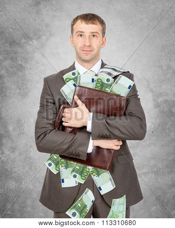 Businessman holding suitcase with piles of euro