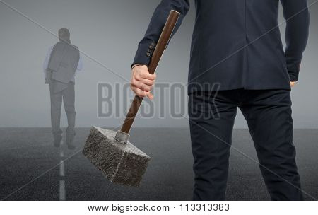 Determined businessman with hammer in hands. Business concept.