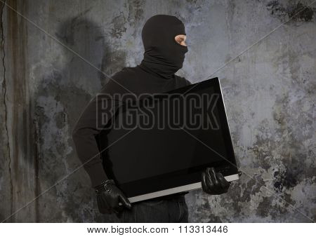 Thief with balaclava stealing computer monitor or television