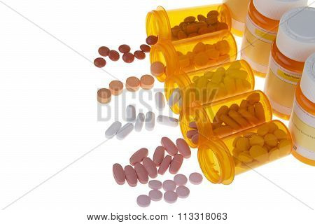 Many pills spilling out onto an isolated white background from orange medication bottles
