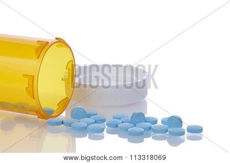 medication bottle on side with blue pills spilling out onto a reflective surface