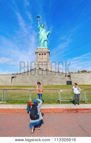 NEW YORK CITY - OCTOBER 13, 2015: Liberty Statue with unidentified people. Its a colossal neoclassical sculpture, designed by Frederic Auguste Bartholdi, built by Gustave Eiffel and dedicated 1886