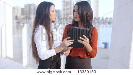 Two attractive stylish young women standing on a waterfront esplanade laughing at a tablet computer as they read information on the screen