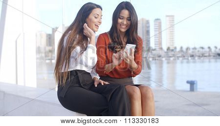 Smiling stylish attractive young woman sharing a text message on her mobile with a friend as they sit together on an urban esplanade