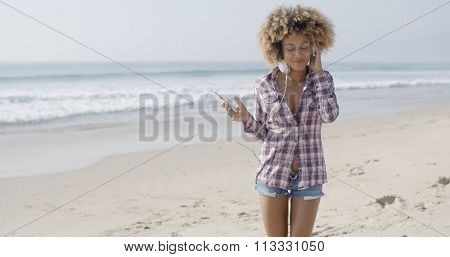 Young woman listening to music and dancing at the beach slow motion