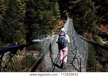 Hiker crossing suspension bridge, Nepal