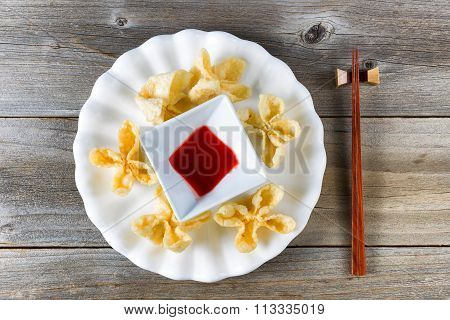 Fried Wanton Shells And Sweet Dipping Sauce In White Bowl On Rustic Wood