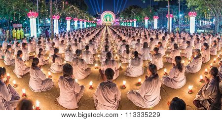 Buddhist panorama sitting hands in prayer in candlelit