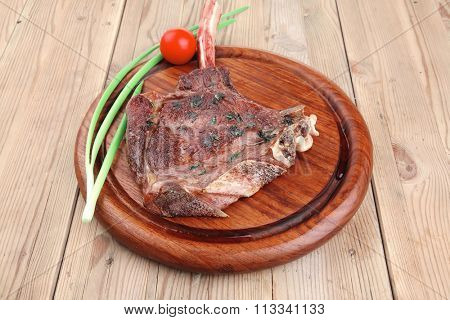 served main course: boned roasted lamb ribs served with green chives and cherry tomato on wooden plate