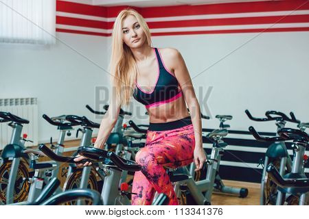 Young blonde woman on a stationary bike.