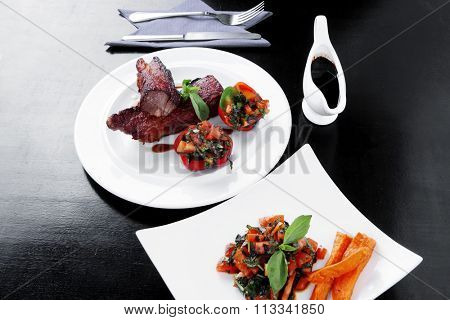 fresh red beef meat steak barbecue garnished vegetable salad and basil on white plate over black wooden table with bbq sauce in sauceboat