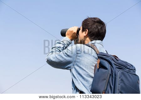 Man looking though the binocular against blue sky