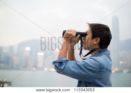 Man looking though the binocular at Hong Kong