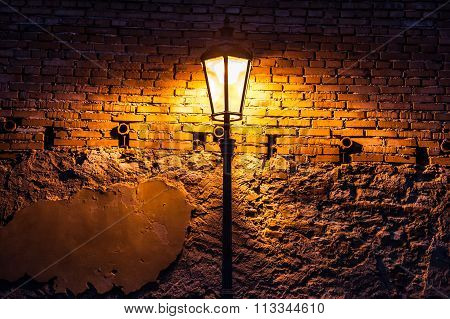 Vintage Street Lamp Against A Brick Wall At Night