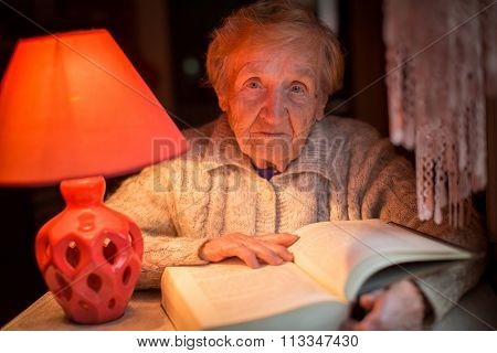 An old woman reads a book under a table lamp at night.