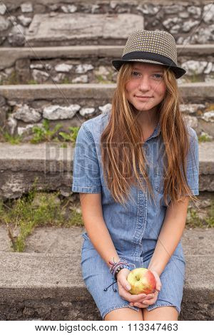 Young pretty girl sitting on the stone steps with an apple in his hand.