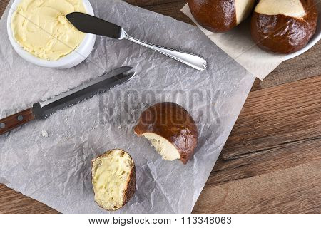 HIgh angle view of a pretzel bun broken in half and buttered. A crock of butter, knife and bowl of whole buns with a broken roll on parchment paper.
