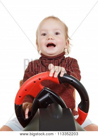 Baby plays a driving game console, isolated on white