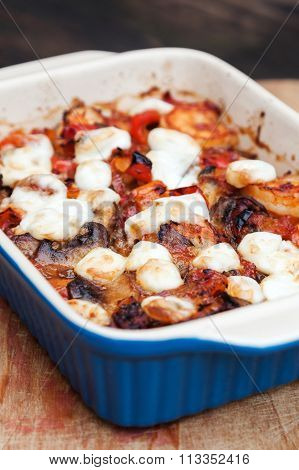 shrimp casserole gratinated with mozarella with dark vignette