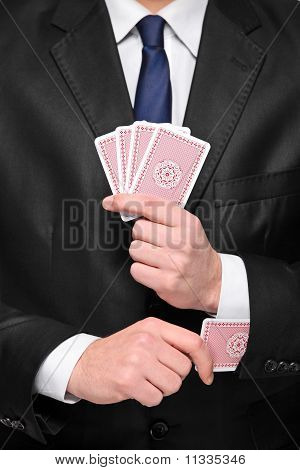 Person Holding Four Cards In His Hand And Pulling One Card From His Sleeve