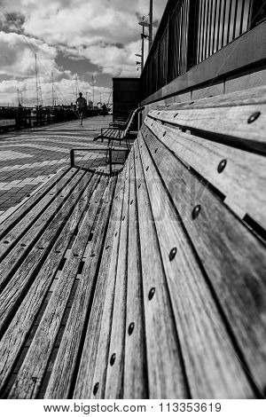 Park bench with jogger in background in black and white