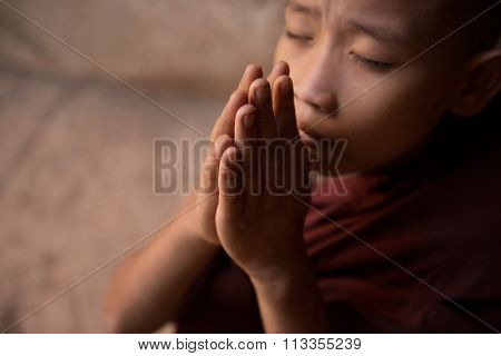Young novice monk praying inside Buddhist temple, focus on hand, Bagan, Myanmar.