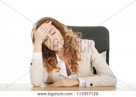 Beautiful exhautsed businesswoman at the desk.