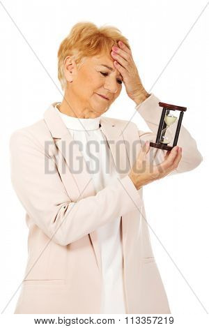 Worried elderly business woman with palm on her forehead holding hourglass.
