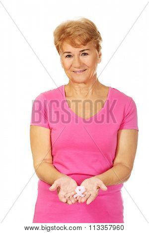 Smiling senior woman with breast cancer awareness ribbon.