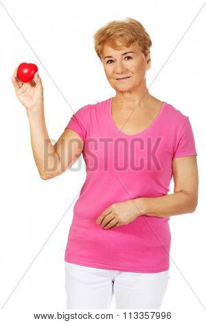 Old smiling woman holding red toy heart.