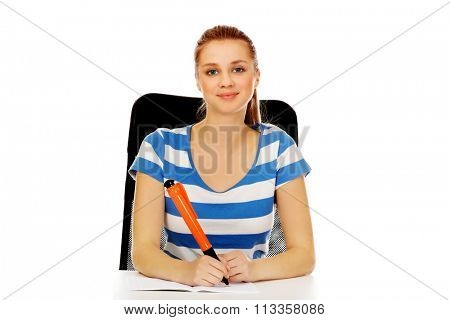 Teenage woman doing notes with a huge pen.