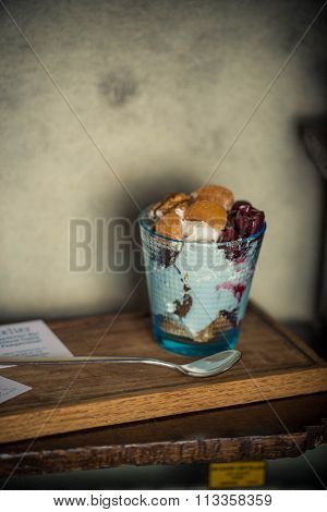 Cream dessert with mandarin oranges and cherries in a transparent glass standing on the table