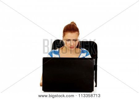 Teenage angry woman with laptop sitting behind the desk.