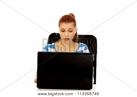 Teenage shocked woman with laptop sitting behind the desk.
