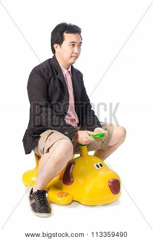 Young Asian Businessman Driving A Baby Toy Car Look Like Dog, Isolated