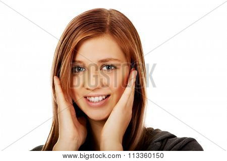 Teenage happy woman holding both hands on cheeks.