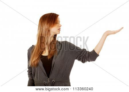 Teenage woman presenting something on open palm.