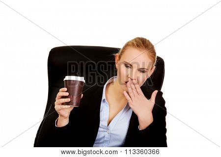 Yawning business woman sitting on wheel chair and holding cup of coffee.