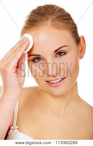 Beautiful woman using cotton pad.