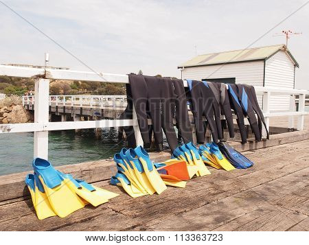 Diving wetsuits for divers drying on a pier