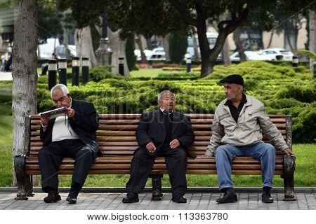 Three men in conversation on a bench in Baku, Azerbaijan