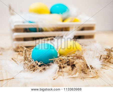 Two Easter eggs in the nest on rustic wooden background.Easter eggs in a box in the background.