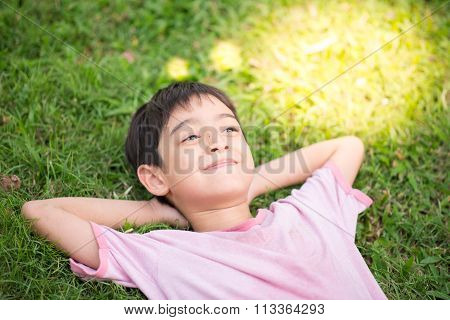 Little boy laying down on the grass dreaming light