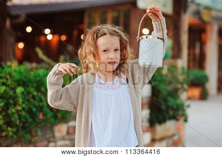 little child girl welcoming guests at cozy evening country house with lantern