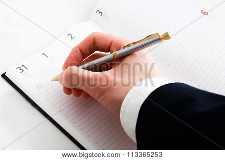 Close up of hand writing and notepad