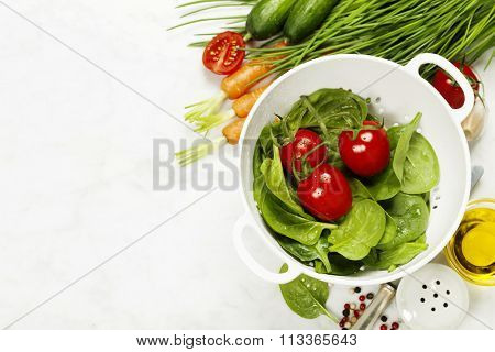fresh organic garden vegetables in colander bowl on white rustic stone background, healthy cooking concept