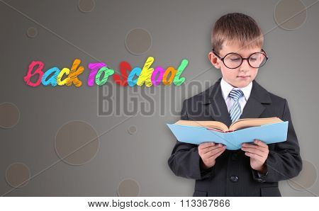 Portrait of boy in school uniform with book, on grey background